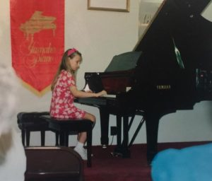 playing the grand piano at a piano recital as a child