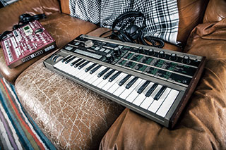MIDI keyboard with a mixer sitting on a worn leather sofa