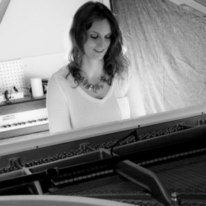 Jacqueline Courson playing on a white Steinway piano
