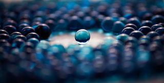 single blue marble in focus among a sea of other blue marbles out of focus