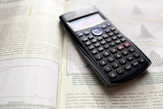 calculator and math book open to page about statistics