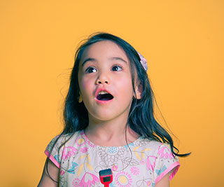 young girl excited about piano lessons while in front of a yellow background