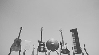 people holding guitars, microphones and a keyboard in the air