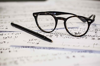 glasses and a pen resting on sheet music