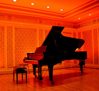 grand piano in a hall with red lights