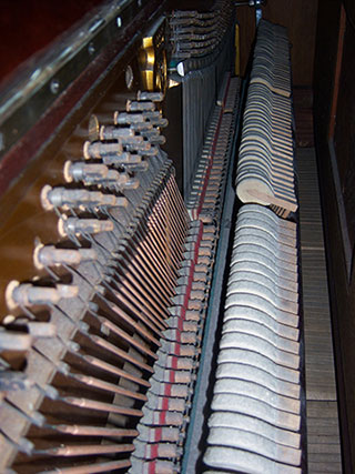 inside of a piano with close up view of strings and hammers