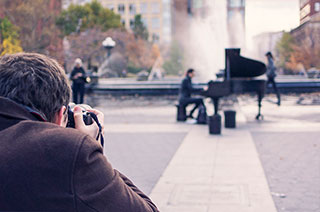 man photographing a man playing a grand piano in the middle of park by fountain