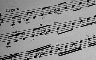 close-up photo of scales on sheet music demonstrating patterns in music