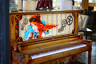 an upright piano with a woman and gears decoratively painted on the front