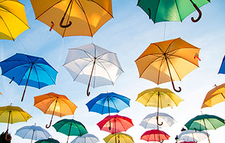 rainbow of umbrellas rising into the sky as weightlessly as if they have come alive